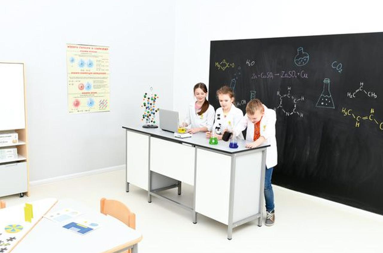 Dzieci na lekcji chemii wykonujące eksperymenty w klasie z wyposażeniem kupionym w ramach rezerwy oświatowej